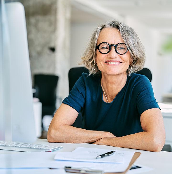 mature woman at desk smiling